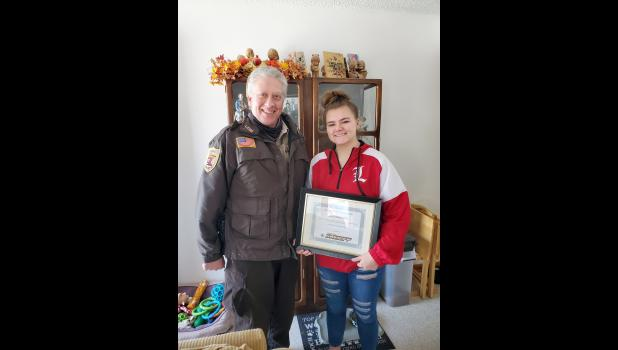 On Christmas Eve, Lincoln County Sheriff Chad Meester (left) drove from Ivanhoe to Luverne to present LHS sophomore Zoe Wek with a certificate of appreciation for her role in a positive outcome from a June 4 boating accident near Lake Benton.