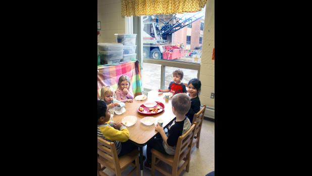 Discovery Time Preschool students (from left) Sean Bonilla Soto, Kayedence Cink, Olivia Rigney, Wesley Kracht, Emrik Syndergaard and Mary Waddington enjoy snack time Friday while construction workers carry on outside at the Luverne Schools construction site.