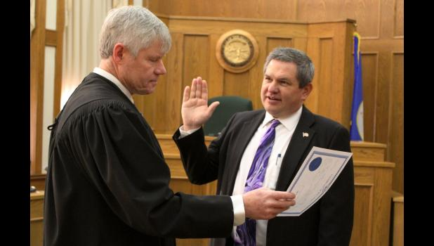 Jeff Haubrich (right) is sworn in as the county attorney Tuesday morning, Jan. 8, in the Rock County Courthouse. District Court Judge Terry Vajgrt administered the oath.