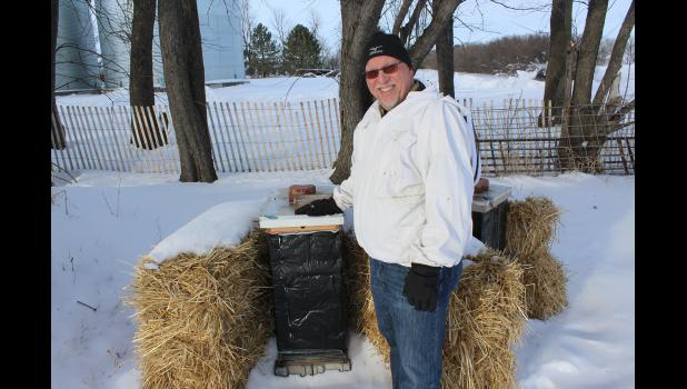 Local beekeeper Tim Olsen poses with two of his honeybee hives northwest of Luverne. Olsen will instruct a class in apiculture on Feb. 25 and March 10 through Luverne Community Education.