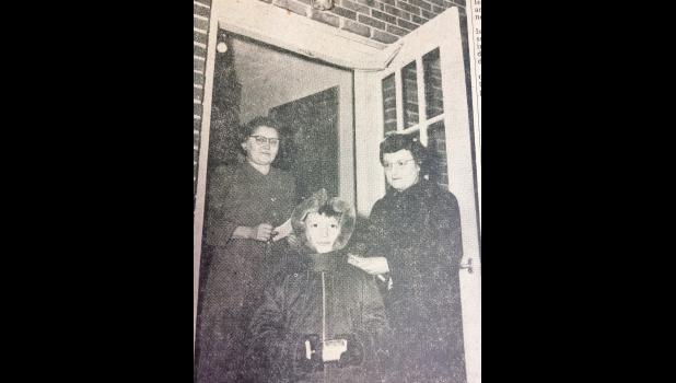 """Lighted porchlights signaled the willingness to give to the March of Dimes drive conducted under the auspices of the Luverne Grade School Mothers' club Thursday night. Typical of the scenes at virtually every Luverne home is this one caught by the Star-Herald's camera at the Henry Untiedt home on North Estey street. Standing in the doorway is Mrs. Untiedt. The """"marching mother"""" is Mrs. James Bagbey. Foreground is Stephen Bagbey who made the march with his mother. In all, 95 Luverne mothers participated in t"""