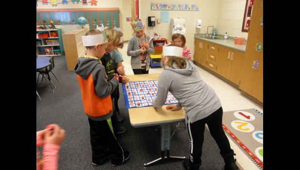 Kindergarten teacher Cathy Rust hid 100 chocolate kisses around her room. Students (from left) Will Boltjes, Saul Hoven, Dakotah Sina, Taya Johnson, AnneMarie Underwood and Ellie VanBatavia found the candy kisses, read the number on the bottom of each and placed it in the correct position on the 100 chart.
