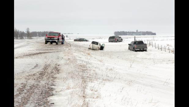 Four motorists find themselves in the ditch Sunday after gusty winds sent snow drifting over roadways causing a long slippery stretch. This photograph was taken in western Rock County on Highway 23.