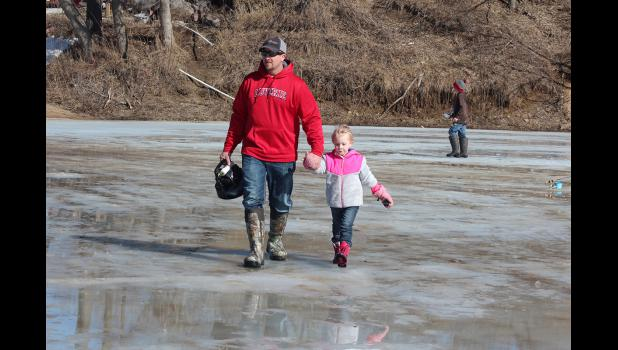 Jesse Frey and his daughter, Juliana Frey, head out across the ice.