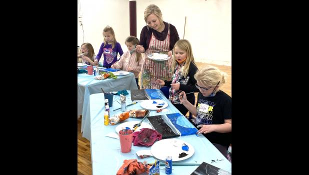 """Local artist McKenzie Wieneke leads a group of aspiring young artists through her Community Education class, """"Paint a Winter Wonderland,"""" Feb. 23 in the Lord Grizzly Gallery building's lower level. The space was formerly used for Luverne Tae Kwon Do, which now meets on the main floor."""