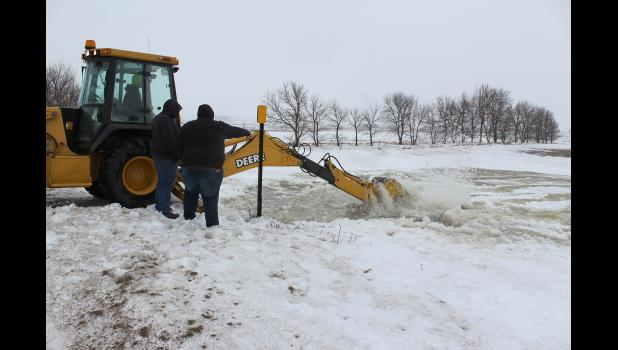 Crews work to clear a culvert on County Road 7 near Hardwick.