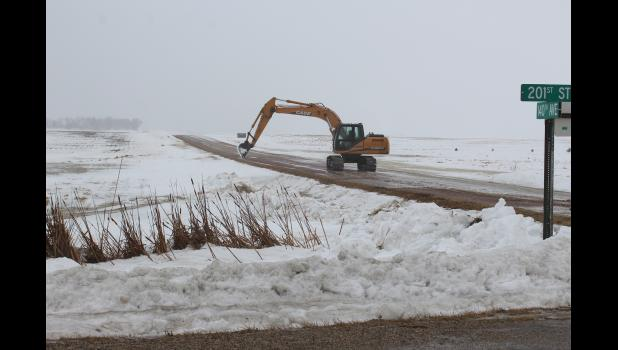 Chad Ver Steeg uses an excavator to remove snow from ditches on the east side of Hardwick, to prevent water from flowing over the roadways