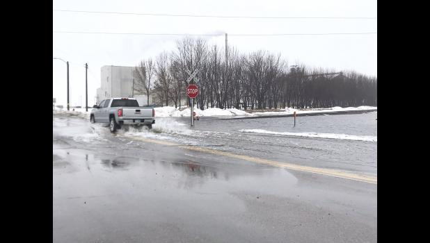 A motorist travels through standing water over the railroad tracks near Gevo in Luverne.