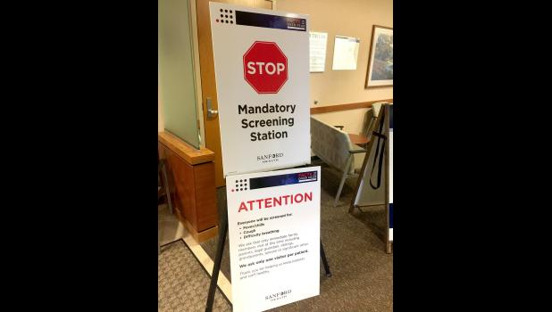 The Sanford Luverne Emergency Room entrance shows visitor policies and serves as a mandatory screening station. There are three entrances facility-wide and all are mandatory stations to screen for potential coronavirus risk factors.
