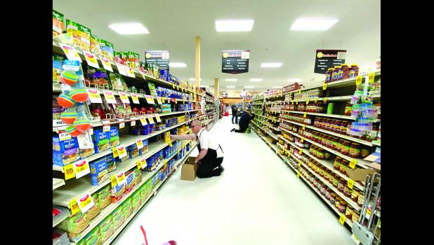 Sunshine store manager Jason Oye stocks shelves in Luverne on March 26.