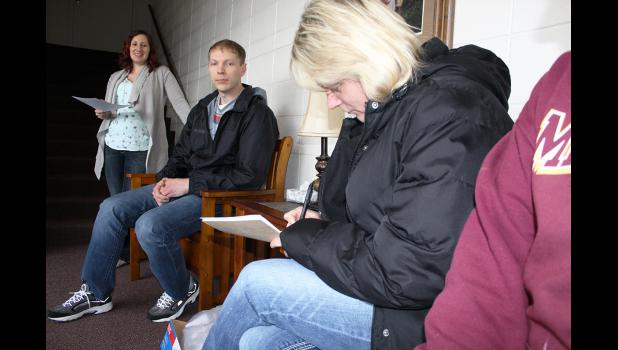 Kristie Weinkauf (third from right) signs her name to the limited liability company form last week as members Elicia Kortus (far left) and Jason Madtson look on.
