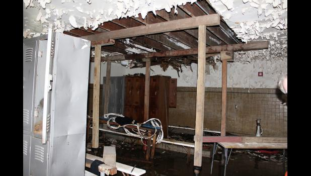 The boys' locker room has suffered the most damage over the years from a roof leak. Workers have raised the ceiling within two inches of the roof.