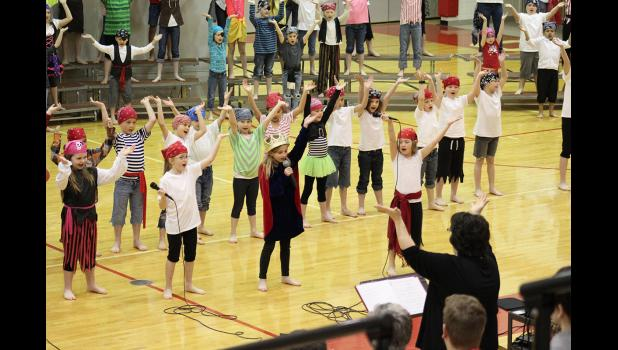 "Singing ""The Queen's Plan,"" fourth-grader Brooklyn Wicks (center) portrays the Queen of the High Seas."