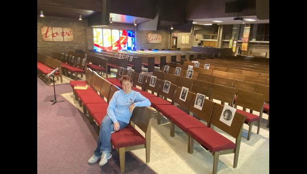 Pastor Dorie Hall sits in the sanctuary of the United Methodist Church in Luverne, where she's taped pictures of congregation members on the pews.