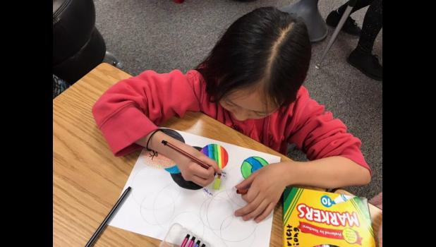 "Luverne Elementary fifth-grader Scarlett Xiong uses her free time to make Circle Art. The newly formed elementary student council proposed creating an ""Expressions is Elementary"" art program. Fundraising for the program began Friday as part of the annual Cardinal Dash."