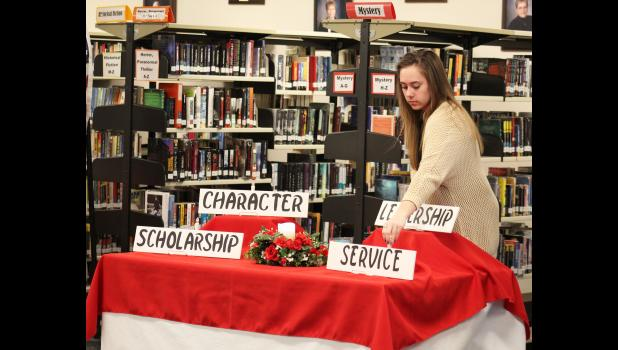 Emilie Staeffler, a senior, places a candle representing service at the National Honor Society induction ceremony April 8 in the Luverne Middle-High School media center.