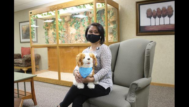 Elena Heronimus, housing manager at The Oaks and Poplar Creek Estates, holds one of two robotic pets used as tools to help calm a resident by providing an interactive companion. In addition to a dog, the assisted living facility also has a cat.
