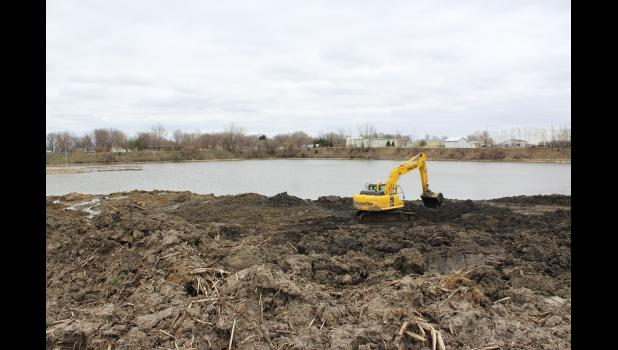"""Henning Construction earth moving crews tackle the northwest shoreline of The Lake in Luverne Tuesday afternoon, April 13. The city of Luverne's """"green space reclamation"""" project will replace a steep bank with a more gently sloping area that can be seeded with grass and used for recreation."""
