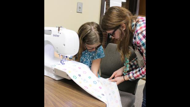 Mira Uithoven (right) points to the area just inside the fabric's selvage to place the next pillowcase seam with 4-H'er Cassandra Chesley.