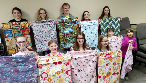 Members of the County K9s 4-H Club helped member Mira Uithoven (front row, third from left) finish an FCCLA community leadership project to sew 50 pillowcases for her Every Pillow Has A Story that will be donated locally. Holding up the completed pillowcases at their April 18 4-H meeting are (front from left) Annaliese Braucht, Riley Anderson, Uithoven, Cassandra Chesley, Aisha Porter, Gabriella Porter, (back) Adayla Rouzer, Alexa Chesley, Adam Fodness, Sophie Holmberg and Candice Porter.