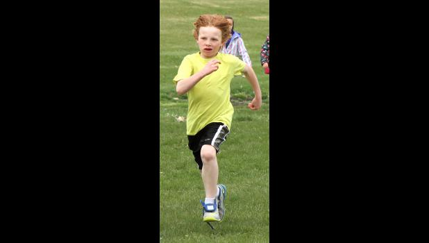 Second-grader Jackson Ganun completes a half-mile run Friday afternoon, April 24, around the high school ball fields.