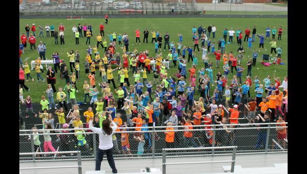 Stacy Kruse leads Luverne Elementary School students, staff and parents Friday afternoon, April 24, on the football field at the conclusion of the first-ever Cardinal Dash.