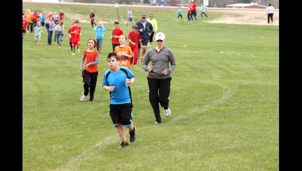 Luverne Elementary School Principal Stacy Gillette (in white cap) encourages runners Friday, April 24, at the new fundraising event called Cardinal Dash. Gillette ran with the third-grade class, who gathered the most pledges as a group.