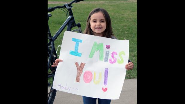 """Preschooler RaeLynn Poncelet holds a sign, """"I Miss You!"""" to teachers as they passed through Steen."""