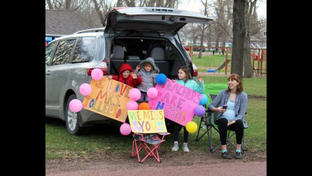 """The Fick family of rural Hills parked near the city park in Hills where they greeted teachers with signs of """"I love Mrs. Tollefson,"""" """"We miss you,"""" and """"Teachers are heroes."""" Pictured from left are Ben, Abigail, Lily and mom, Lisa."""