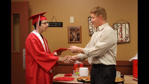 Juan Carreon receives the vinyl folder that will hold his Luverne High School Class of 2015 diploma from Principal Ryan Johnson earlier this month. Carreon worked through the school's alternative school to achieve the diploma that only a handful of members in his family have achieved.