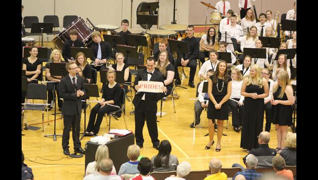 """Band seniors present director Richard Owen with a parting gift at the concert Friday, April 24. It's a wall hanging that says, """"Pride,"""" because Owen encourages them to take pride in their work. The gift hadn't shipped yet, so the students wrapped a piece of paper."""