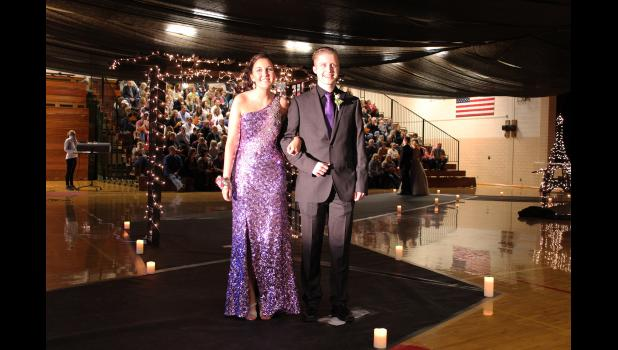 Pausing before the audience members in the south side bleachers, Melissa Tweet and Chase Wiederhoeft strike a pose Saturday night during Luverne High School's Grand March. The duo was among 102 couples who participated in the annual spring tradition.