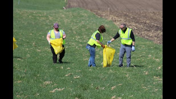 Samantha McGaffee, Renee Edmondson and Superintendent Todd Holthaus work along the ditches between Hills and Steen.