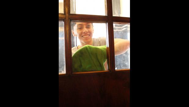 Omar Martinez Pizano cleans windows at the Palace Theatre.