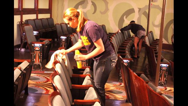 Naomi Dooyema and Audrey Emery work at polishing the 450 wooden seats at the Palace Theatre.