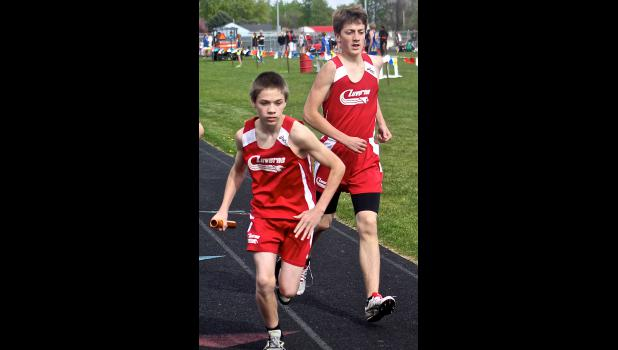 Jordy Thone (left) begins his leg of the 3,200-meter relay after taking the baton from Austin Winter Tuesday in Luverne.