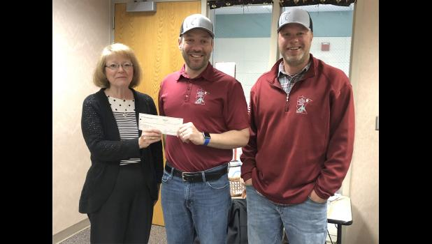 Cindy Arends (left) accepts a check on behalf of the Backpack Program from Lucas Peters (center) and Eric Benson from the Rock County Corn and Soybean Growers board.