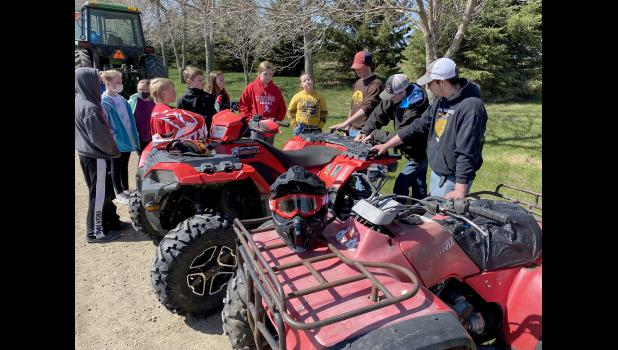 Fourth-graders (from left) Nolan Dekam, Allison Beyer, Summer Mollberg, Ty Kopp, Will Gehrke, Makenzie Smith, Gracyn Woodley and Naima French learn about ATV safety from FFA'ers (from left) Chris Aning, Harrison Uithoven, and Lucas Hansen
