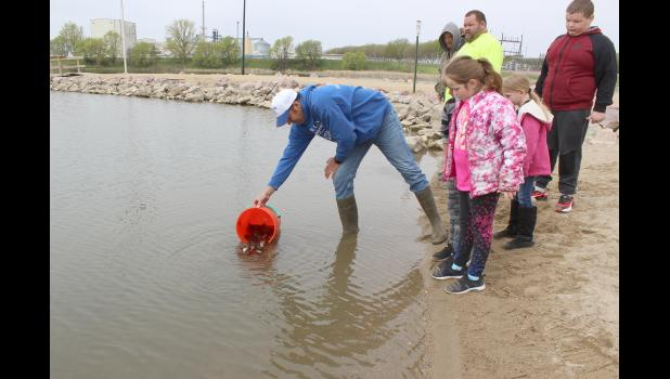 Releasing the young bluegills into the lake are is John Chambers (left) and watching (from left) Summer Aning, Jeremy Wallenberg (back), Dustin Aning, Emmalee Wallenberg and Danny Aning.
