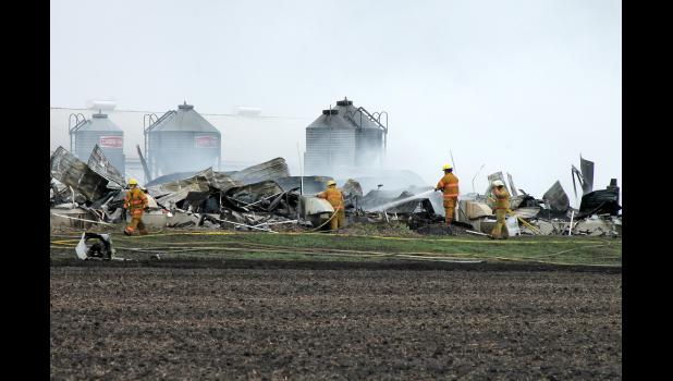 Area fire and rescue personnel work Monday to extinguish the blaze at this hog barn fire east of Jasper that took the lives of two Jasper women.