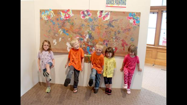 Carolynn Baustian's day care group shows how they danced on paper creating the art work hung behind them. They are (from left) Myah Johnson, Barrett Rodman, Dallas Erickson, Josie Garcia, and Sophia Baatz.