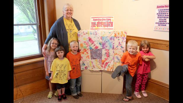 Carolynn Baustian and her day care kids pose in front of their art work.
