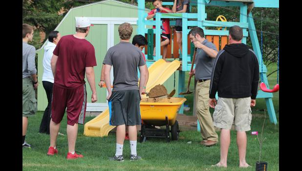 Luverne Optimist Club members fill a sandbox.