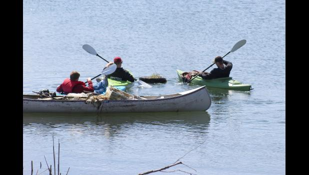 Senior Michael Kinsinger (far left) maneuvers his kayak pulling a canoe full of garbage removed from The Lake. Tom Brown (center) and Gaige Nath push a discarded tire to shore.
