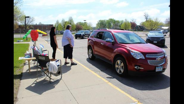 Discovery Time Teachers Angie Janiszeski (left) and Becky Runnoe visit with preschoolers Thursday morning, May 14, in the parking lot of Luverne Elementary School.