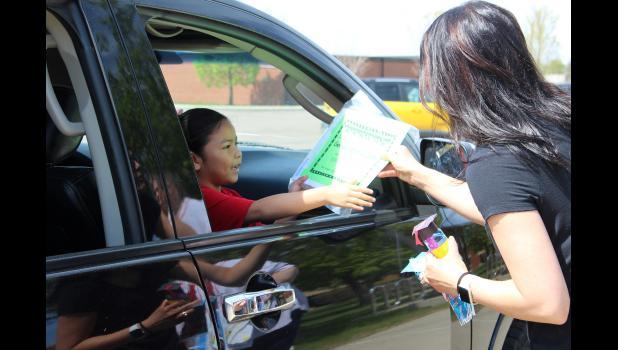 Preschooler Genesis Bonilla Soto receives her school certificate from teacher Angie Janiszeski.