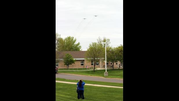 Stephanie Sparks and her son, KC, of Beaver Creek, videos the two C-130s, as they fly over the Minnesota Veterans Home in Luverne.