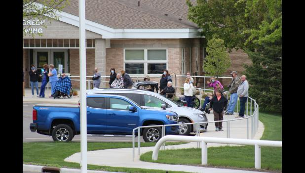 Minnesota Veterans Home residents and essential workers wait for two C-130s to fly a training mission over the long-term care facility.