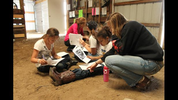 Rock County 4-H Horse Project veteran Joanna Westphal (far left) points to the equitation questions for a crossword puzzle with horseless project participants Mia Wenzel and Tyrae Goodface. Pictured (from left) are Goodface, horseless helpers Thea Richards and Andrea Severtson, Wenzel and Westphal.