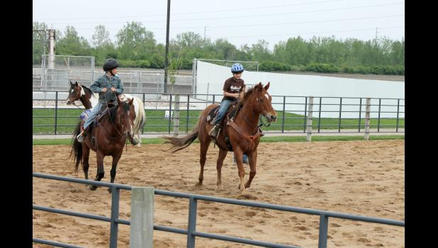 Young riders Chance Heyden and Cash Bonnett take their horses around the fairground's arena during Rock County 4-H's first night of weekly horse riding sessions on Wednesday, May 13, in Luverne.